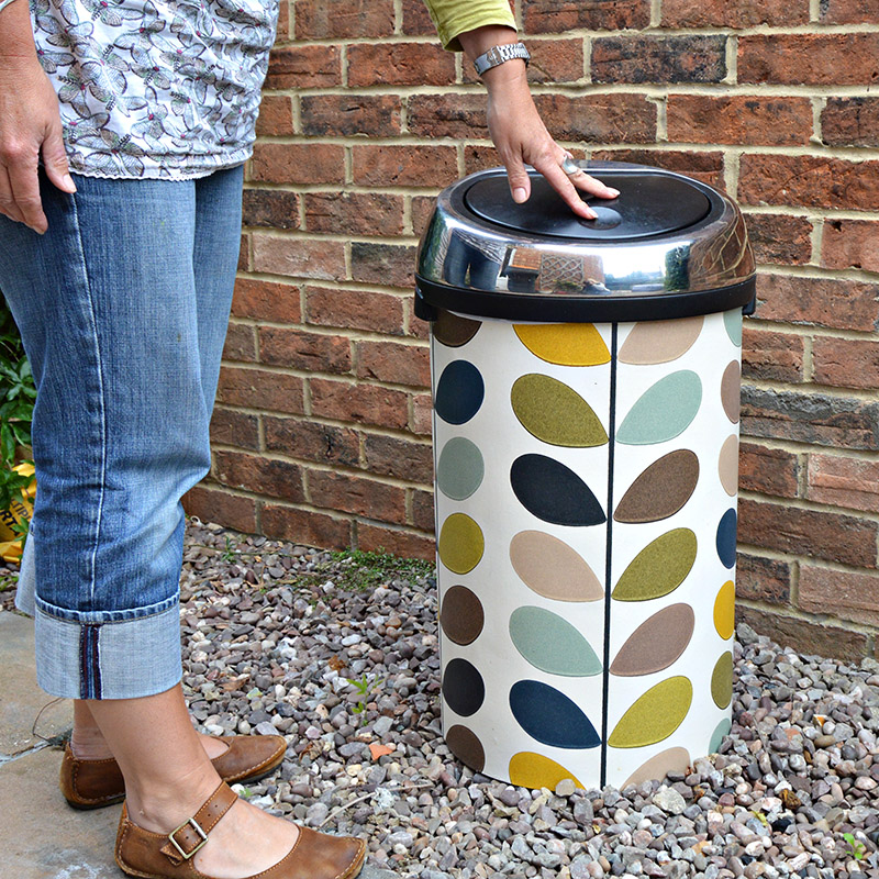 Give a plain trash can a makeover by covering it with pretty wallpaper