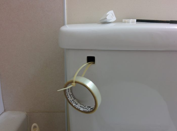 Fix the broken toilet handle using zip ties and tape